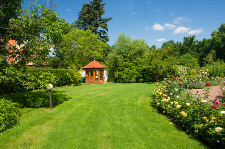 summer house: Beautiful garden with blooming roses, brick path and a small gazebo Stock Photo