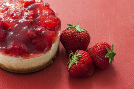 cream cheese: Small strawberry cheesecake on a red background