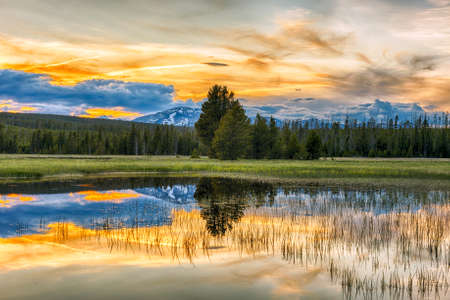 Beautiful vivid sunset at Yellowstone National Park. Mountains and sky is reflecting in a lake. Wyoming, USA Stock Photo