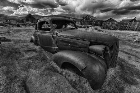 oxidado: Restos de un coche oxidado antigua en un pueblo fantasma de Bodie. Bodie es un monumento histórico nacional. Se encuentra en el condado de Mono, Sierra Nevada - California. Estados Unidos de America. En blanco y negro Foto de archivo