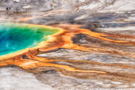 Deatiled photo of Grand Prismatic Spring from above with unrecognizable tourists watching it. Yellowstone National Park, Wyoming, USA