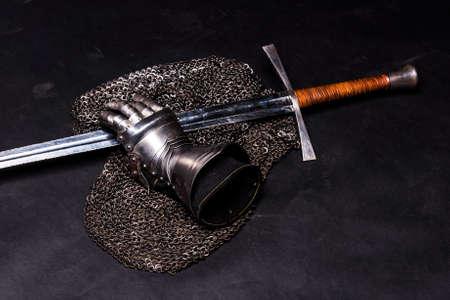 bastard: Medieval chain mail, iron gauntlet and a bastard sword still life on a dark background Stock Photo