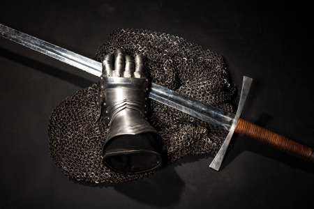 Medieval chain mail, iron gauntlet and a bastard sword still life on a dark background Stock Photo