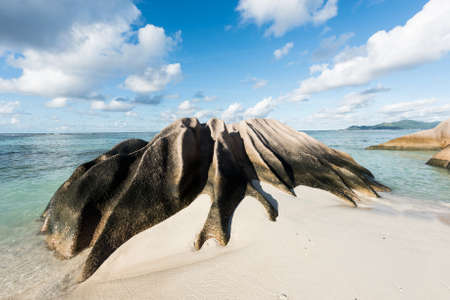 Beautifully shaped granite boulders and a perfect white sand at the famous Anse Source dArgent beach, La Digue island, Seychelles. Panorama Stock Photo