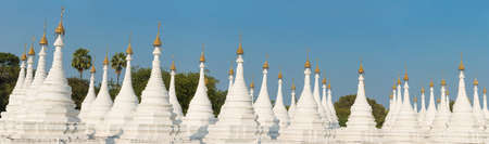 Kuthodaw Pagoda contains the worlds biggest book. There are 729 white stupas with caves with a marble slab inside - page with buddhist inscription. Mandalay, Myanmar Stock Photo