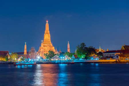 Large illuminated temple Wat Arun after sunset seen accross river Chao Phraya. Bangkok, Thailand Stock Photo