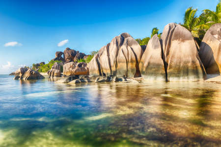 Beautifully shaped granite boulders reflecting in the water at Anse Source dArgent beach, La Digue island, Seychelles