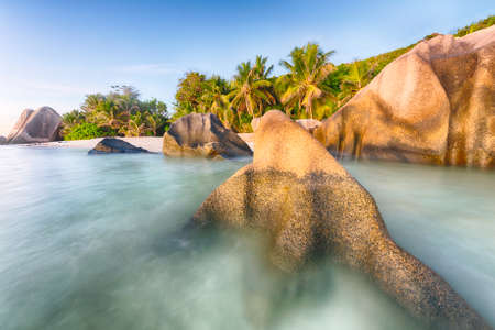 d'argent: Beautifully shaped granite boulders during sunset  at Anse Source dArgent beach, La Digue island, Seychelles. Long exposure Stock Photo