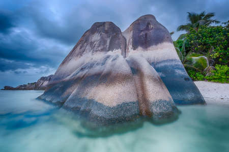 anse source d argent: Beautifully shaped granite boulders in the sea of Seychelles at Anse Source dArgent beach taken with a long exposure. Dramatic stormy sky at sunset time Stock Photo