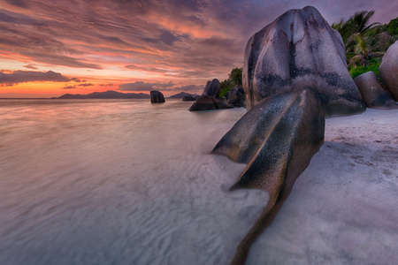 Beautifully shaped granite boulders and a dramatic sunset  at Anse Source dArgent beach, La Digue island, Seychelles Stock Photo