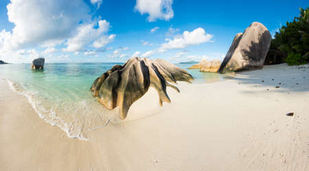 argent: Beautifully shaped granite boulders and a perfect white sand at the famous Anse Source dArgent beach, La Digue island, Seychelles. Panorama Stock Photo