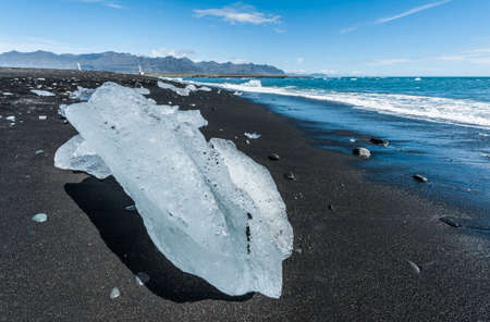 Beautiful beach in the South of Iceland with a black lava sand is full of icebergs from glaciers not far away Stock Photo