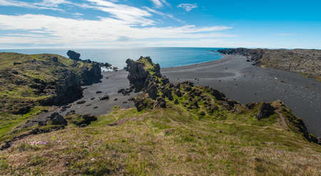 Black sandy Djupalonssandur beach seen from the cliff at Drtivik. Snaefellsnes Peninsula, Iceland. Panorama