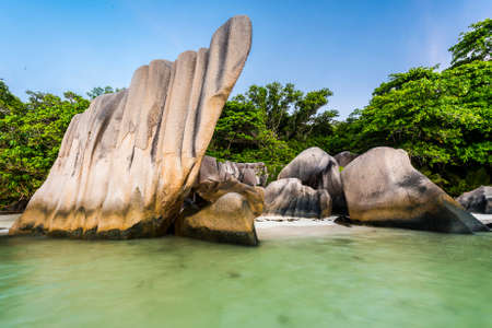 Beautifully shaped granite boulders and a dramatic sunset  at Anse Source dArgent beach, La Digue island, Seychelles. Long exposure with blurred sea Stock Photo