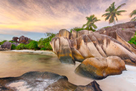 argent: Beautifully shaped granite boulders and a dramatic sunset  at Anse Source dArgent beach, La Digue island, Seychelles Stock Photo