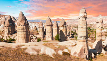 Fairy chimney rocks are dramatically lit by a sunset in Cappadocia, Turkey