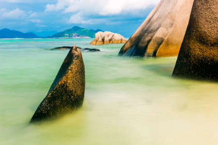 Beautifully shaped granite boulders in the sea of Seychelles at Anse Source dArgent beach taken with a long exposure. Dramatic stormy sky