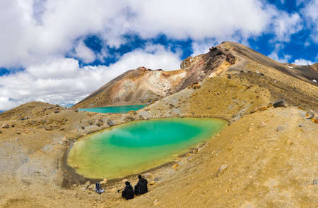 View at two hikers sitting in front beautiful Emerald lakes and watching Mount Ngauruhoe on Tongariro Crossing track, Tongariro National Park, New Zealand Stock Photo