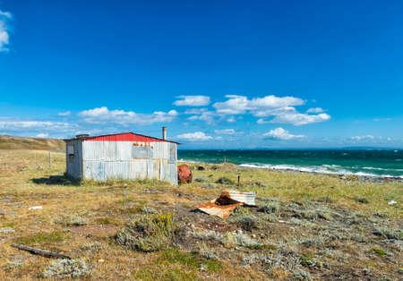 Red fishermans cottage near the coast. Tierra del Fuego, Chile Фото со стока