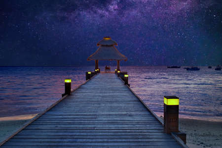 Romantic pair sitting on the jetty under the stars by the sea in the Maldives Stok Fotoğraf