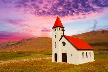 Lebhafter Sonnenuntergang über der schönen kleinen isländischen Kirche in der ländlichen Gegend unter den mächtigen Fjorden Standard-Bild