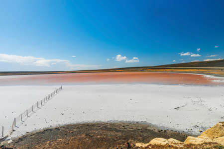 old rusty fence in a salt lake with crystal coated stones in Tierra del Fuego in Argentina.