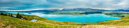 Panoramic picture of  incredibly blue lake Tekapo with overcast sky seen from Mt. John observatory. Canterbury region, New Zealand