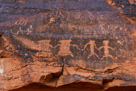 Ancient rock art (petroglyphs) by Ancestral Puebloans - native Americans - seen during hiking at Mouse's Tank hiking trail in Valley of Fire State Park. Nevada in USA