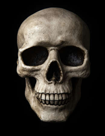 Frontal view at human skull with dramatic lightning is isolated on a black background