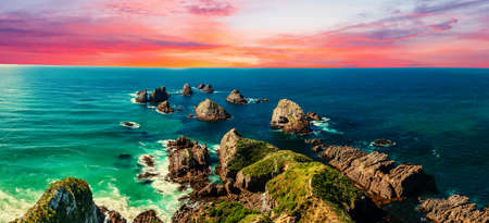 Sunset over Nugget Point which is located in the Catlins area on the Southern Coast of New Zealand. There area many rock islands - nuggets - in the sea. Panoramic photo Stock fotó