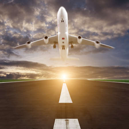 airplane landing: passenger plane fly up over runway from airport at sunset Stock Photo