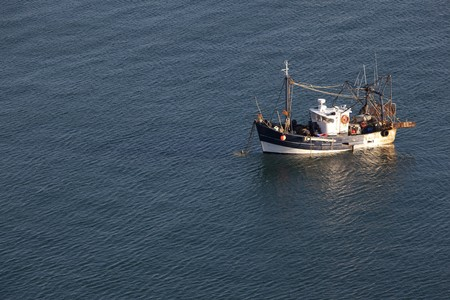 Fishing boat in the middle of the ocean seen from above