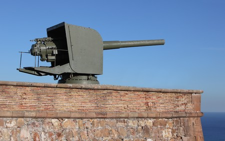 Turret mounted artillery gun in old fortifications photo