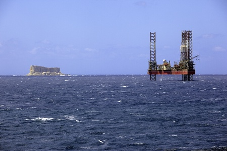 Offshore prospection platform next to a small island in mediterranean sea Stock Photo