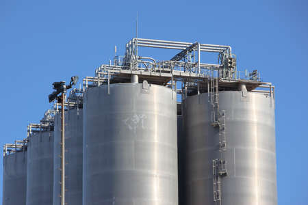 Detail of top of silos in an oil refinery over blue sky