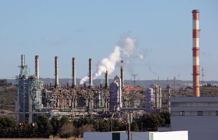 Towers and chimney in oil refinery over blue sky photo