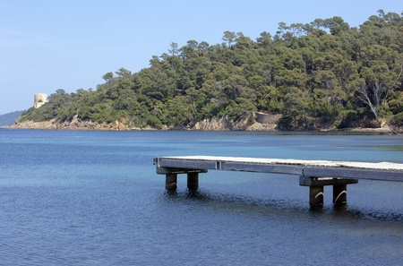 cros: Old wooden pontoon over blue mediterranean sea. Port Cros national park, France Stock Photo
