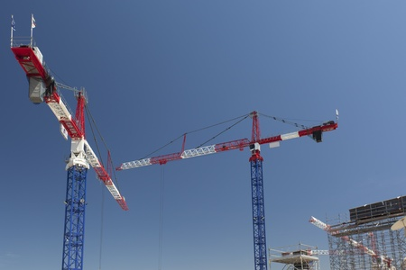 Red and white cranes on a construction site photo
