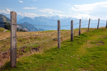 Barbwire fence in the countryside with mountains in the background photo