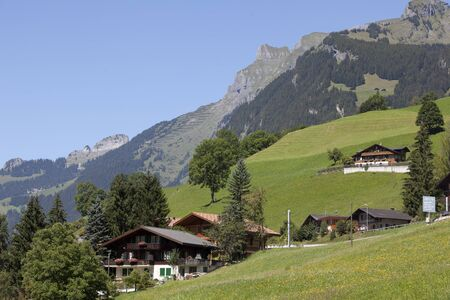 moutains: Traditional Swiss chalets with moutains in the background Stock Photo