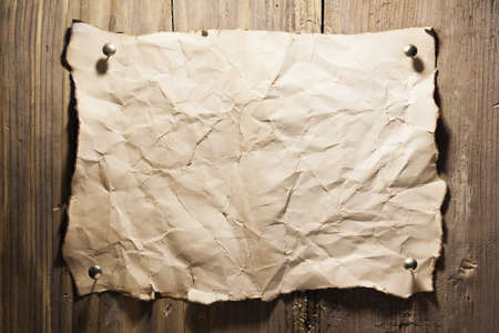 nailed: Old crumpled paper nailed to a wooden wall Stock Photo
