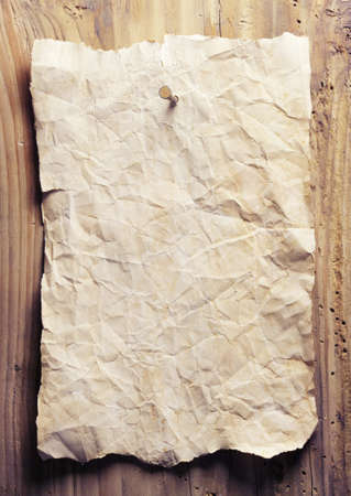 crumpled: Old crumpled paper is on a wooden wall