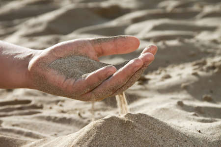 Sand flowing through your fingers photo