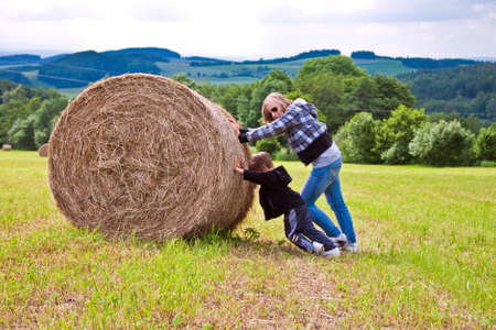 A girl and a boy pushing a round bundle of straw. photo