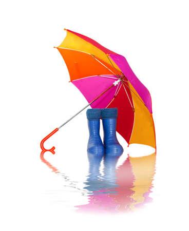 botas de lluvia: botas de goma y un paraguas de colorido con reflejo en el agua