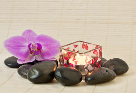Pink orchid and zen Stones with a candle photo