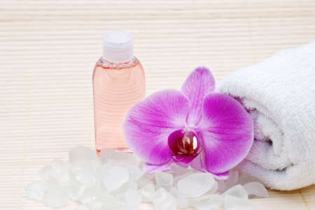 Pink orchid, white towels and bath salts. Spa set photo