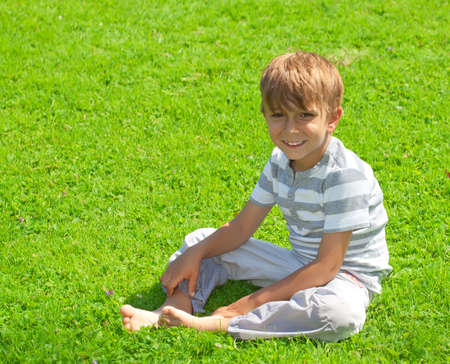 Portrait of a young boy sitting in the grass photo