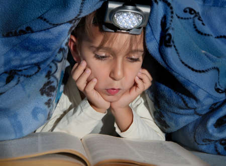 reading lamps: Boy reading a book under the covers with a flashlight Stock Photo