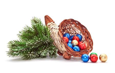 Cornucopia of chocolate balls and pine-branch.